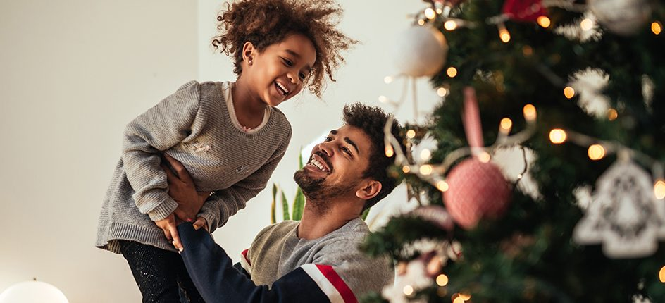 girl and father figure laughing near Christmas tree