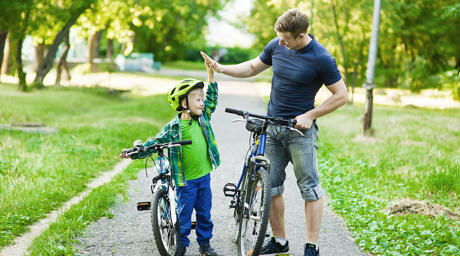 young boy high fiving older man next to bikes
