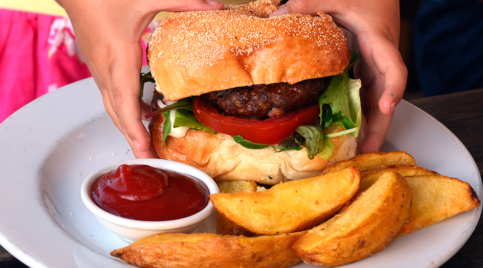 Child Reaching for Hamburger and Fries