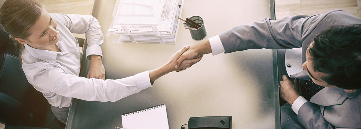 Man and woman shaking hands over desk in office