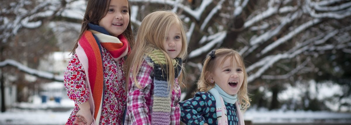 Three girls smile while standing outside in the snow.